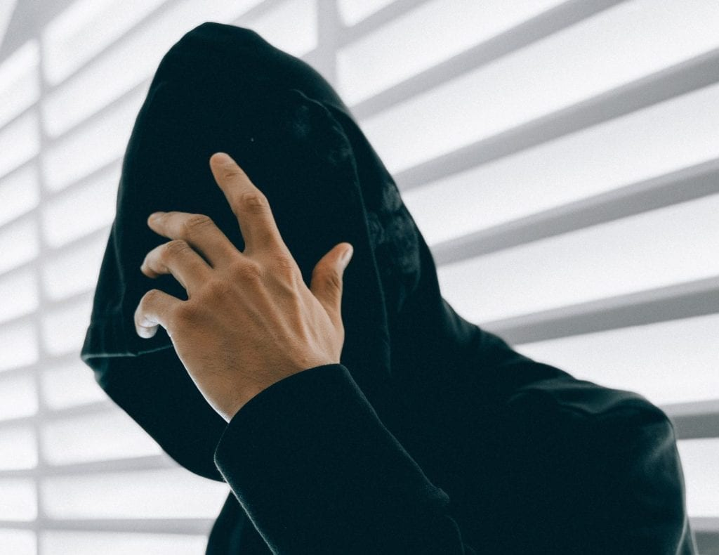 Cyber criminal wearing a black hood