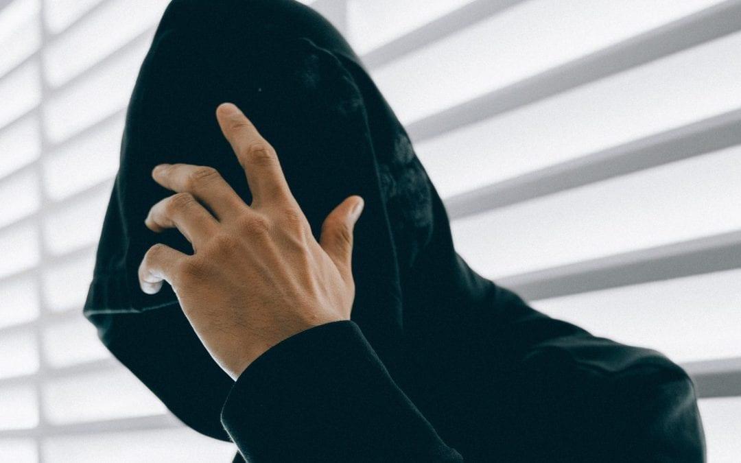 Cyber criminal wearing a black hood